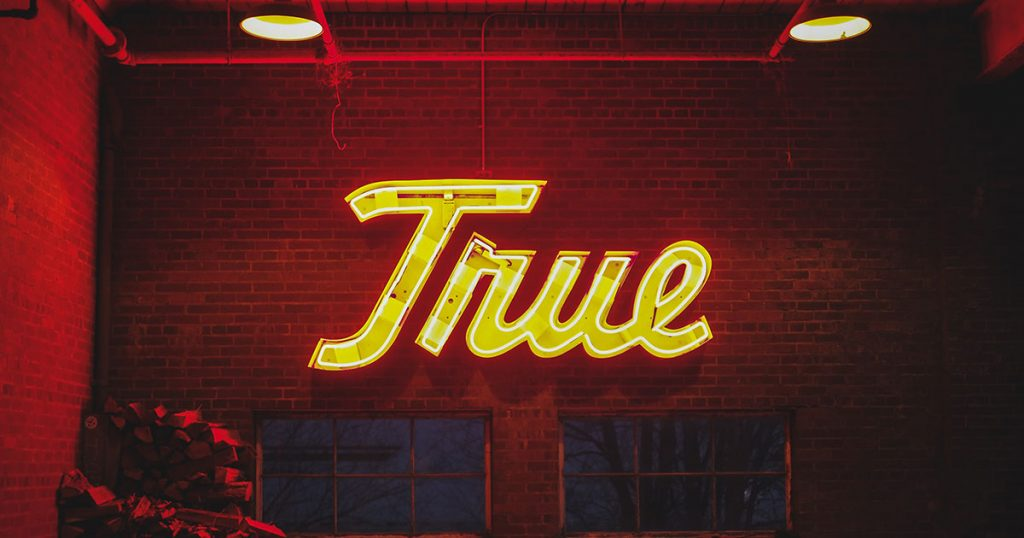 "A lit sign with the word ""true"" on it."