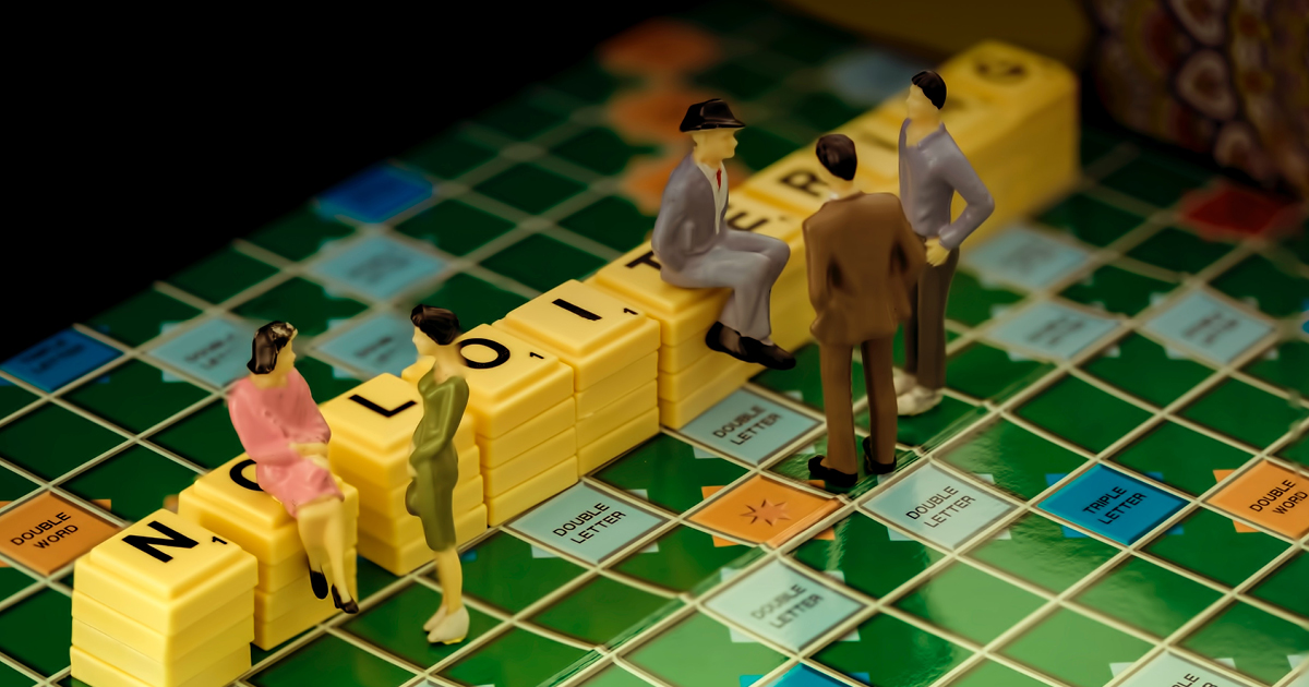 model of people sitting on a scrabble board with the tiles spelling out loiitering to illustrate the blog post titled how to get your content quicker.